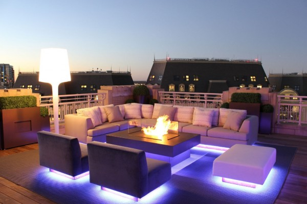 Modern outdoor furniture appears to float on dramatic up-lights.