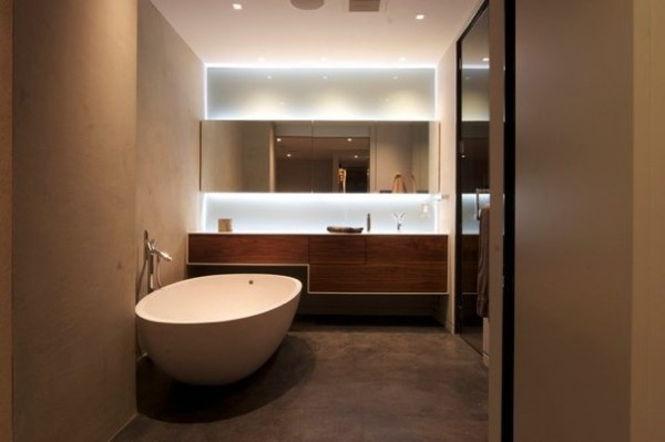 The master bathroom boasts a clean minimalist look with a single soaking tub, sleek wood cabinets and concrete floors.