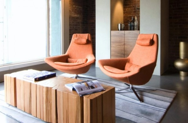 Modern furnishings give the place a mid-century appeal. The twin armchairs in orange add a pop of vivid color in the living space.