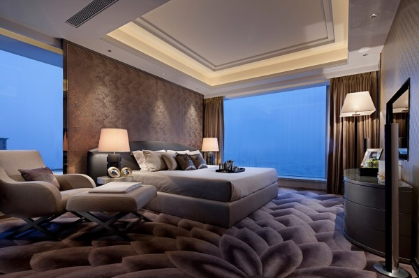 A dynamic rug in an Asian lotus design adds movement and drama to this penthouse apartment bedroom. A large oversize armchair and ottoman offers a wonderful place to relax.