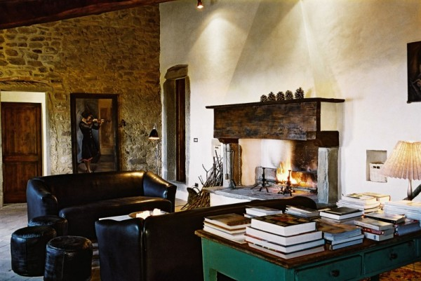A manor house cannot be complete without a fireplace of course, and Casa Bramasole is not lacking in that respect. The exposed brick is a great backdrop for the main living area which also features leather couches and an antique desk loaded with books.