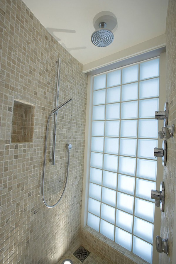 Glass blocks offer naturally lighting in the master shower with its luxury fixtures of rain shower head and multi-directional wall heads.