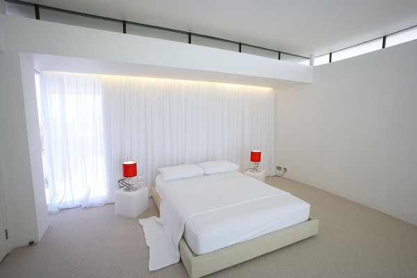 Red table lamps offer a pop of color in this all white minimalist bedroom.