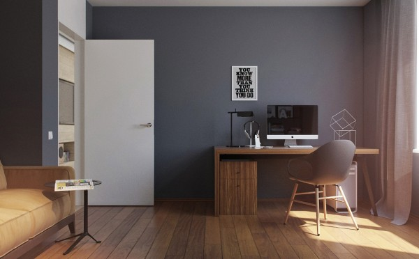 A view of the home office shows a simple yet richly grained wood desk and modern armchair in grey with natural wood base. The wide plank wood flooring adds to the warmth of the space.
