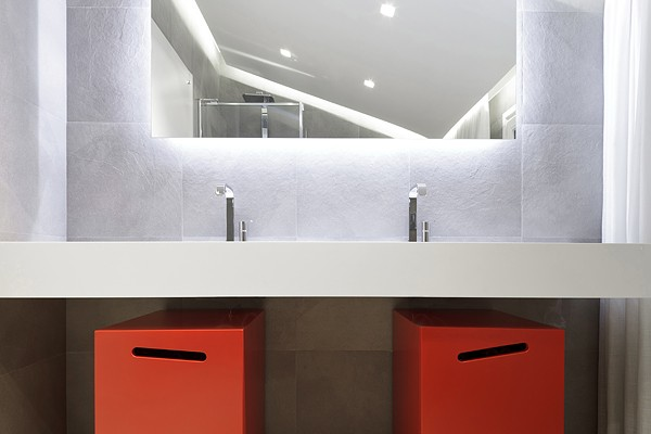 Red storage bins offer the only pop of color in the white bathroom.