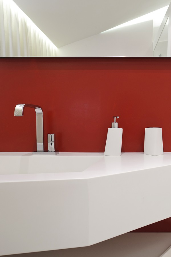 The guest bathroom gets a splash of color from a brick red wall amping the liveliness of the space.