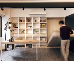 This modern office space quickly becomes a bedroom retreat with a Murphy bed hiding in the wall. It is a smart use of the space as even when the bed is set up, you're still able to function in the office without interference.