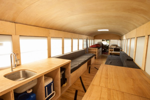 This photo shows the entire length of the converted bus home. The furniture is simple wood and the floor is made of reclaimed gym flooring. None of the structures built go above the window line keeping it linear and open to outside light.