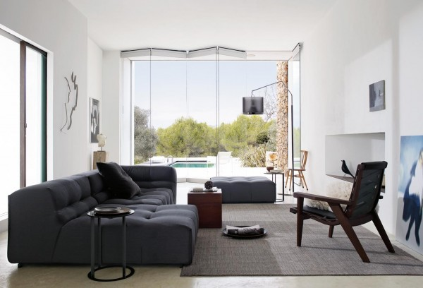 Dark gray fabrics and cherry wood finishes complete this space. It is comfortable yet stylish, and has natural touches exemplified by the retractable glass doors which open to the outside.