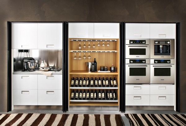 This recessed kitchen wall makes great use of a small space. Cabinets, preparation space, appliances, wine racks and glass storage are all included in this one wall in a neat and organized layout.