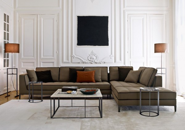 The same piece previously shown in a more subdued color gives another option for someone who isn't as adventurous with their design. This brown sectional with black trim provides contrast in this white room. The square coffee table and circular end tables have the same structural design, even if the shapes differ.