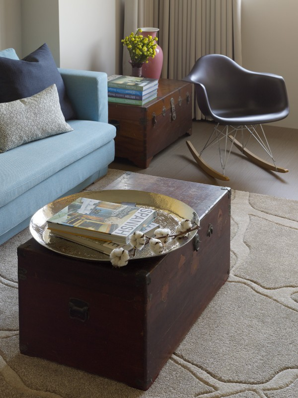 A pair of vintage trunks repurposed as tables give additional storage and a creative feel. The area rug, though a neutral color, brings in elements of nature in its rock pattern that mimics the bed of a flowing creek.