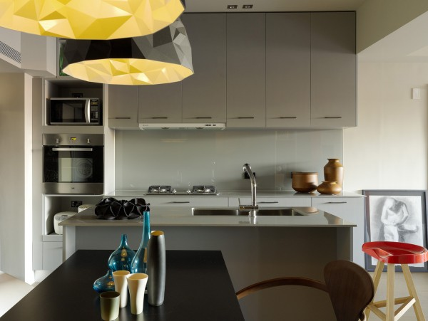 The kitchen is compact but has all the necessities as well as smooth, clean lines that make it an inviting place to prepare any meal. Geometric light fixtures are fun as well as flattering as they softly scatter wattage.