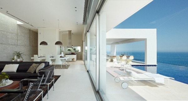 The white also acts as a reflective surface for the many sources of light that have been included in the modern design. Not only does sunlight flood in from the floor-to-ceiling windows that face the sea, but a unique skylight crowns the living area's concrete accent wall, letting sun in from above as well. At night, soft lighting from many hanging fixtures bring necessary visibility without harshness.
