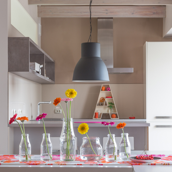 Urban kitchens have a tendency to be small. By keeping the color in the kitchen nook more neutral, the space feels more comfortable. The addition of fresh flower arrangements makes for a welcoming dining atmosphere.