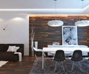 Rich wood covers the floor and feature wall of this otherwise white apartment design, from arhform architectural studio, creating a warm and welcoming look. The lounge and dining areas are defined by shaggy area rugs from a neutral palette, and lighting choices throughout are big and bold.