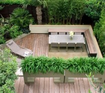 We love the feathery privacy screening created by the border of leafy green plants in this one, as well as the tropical jungle-like borders to make you feel as though you are sunbathing in the rainforest rather than perched above a concrete jungle. The decking runs from edge to edge, giving this space the feeling of an indoor room.