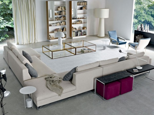 In this very white décor scheme, contained within the border of a long L-shaped sofa, the two areas that really jump out are the pink occasional stools, and the blue accent chairs. This little color blast feature is a good way to liven up any overly neutral scheme you have-you can even use items you already have in other parts of the home, from rooms that are decorated in a completely different color to the one you are accessorizing!
