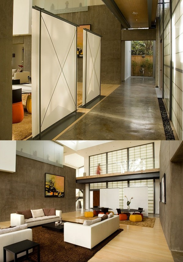 Translucent walls separate a concrete hallway from a contemporary living room with a Japanese flair.