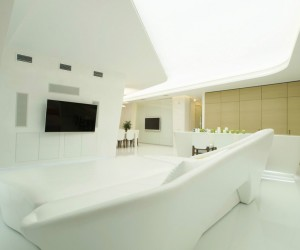 In the living room, a white sofa that would look at home in a spaceship swoops into position in front of a TV wall that has an integrated sound system and concealed media cabinets beneath the screen. The ceiling cutaway forges a path from the lounge area around to the kitchen and dining spaces, revealing an overhead river of light.