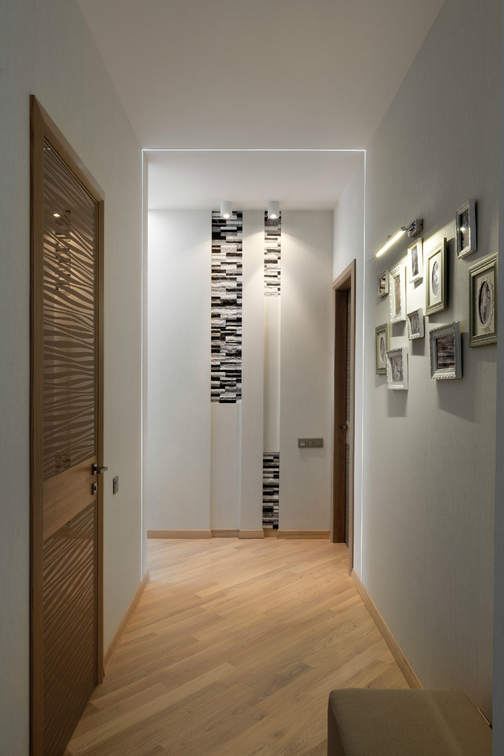 Slim picture light illuminates a family photograph gallery in the