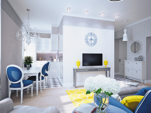The open plan living area is arranged around a central column where a subtle gray console table is brightened by two sunshine yellow vases at each end. The colorful additions are contrasted by a blue wall clock above the flatscreen TV.
