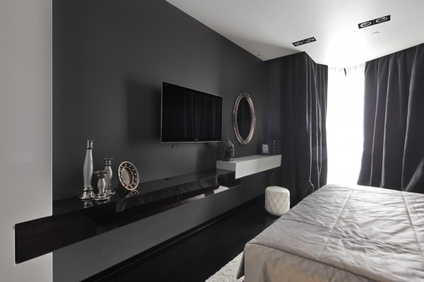 In the bedroom the black wall covering give way to a slightly softer slate gray hue with a matt paint finish, upon which wall mounted consoles collide to form storage for entertainment equipment under the television, and a vanity shelf beneath a classical oval mirror.