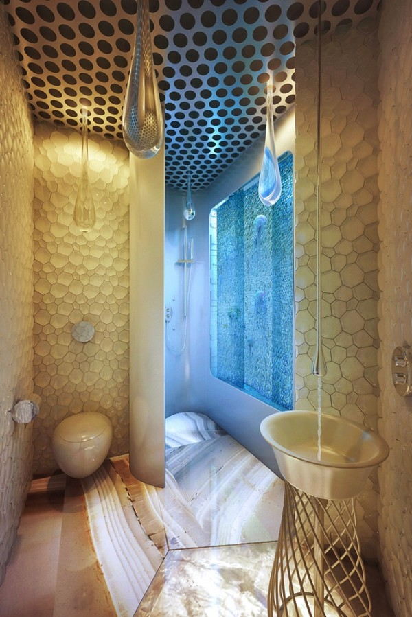 Shell-like wall tiles adorn the bathroom, where the lighting and faucet 'drip' from the ceiling.