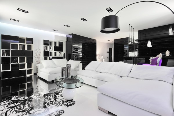 Above the unique floor design, more sleek black and white furniture pieces demand attention along with high shine wall treatments, whilst the large sofa stays understated under plain white upholstery and cushions.