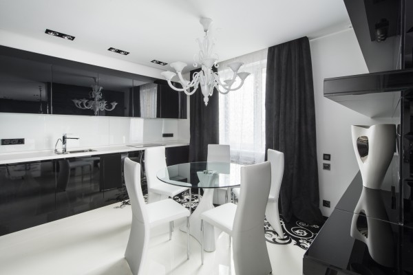 A large and ornate chandelier is knocked back in simple white, creating a ghostly reflection upon the mirror gloss black kitchen cabinetry.