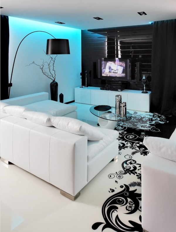 Blue LED lighting adds an injection of cool color over proceedings in the lounge  entertainment area, where the TV springs to life from the black background. A large arc lamp is on hand to cast more practical task lighting.
