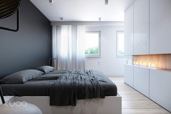 In the bedroom the sombre wall color is repeated, but faces a glossy white run of floor-to-ceiling light reflective units that sit above and below a letterbox open-flame fireplace.