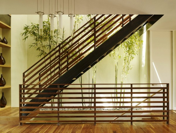 A narrow strip of landing space is utilized in this home with the installation of a long planter, enabling the planting of a path of bamboo that stretches up the staircase.