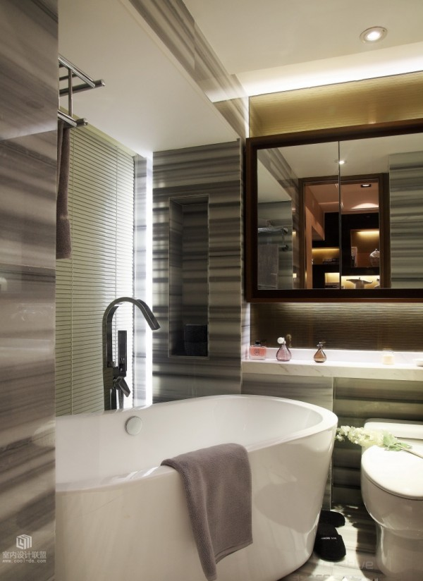 Behind a sliding door, the master bedroom en suite bathroom finds perfection in its compact dimensions. Smooth gray grained tiles luxuriously encase the space, where a modern freestanding bath spans a cozy corner position.