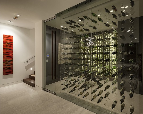 This wine room/cellar houses a wine tasting area, viewable through the vast transparent bottle rack, where friends can sit, sample and sip away the evening.