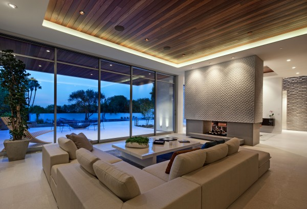 The stylish lounge has an open view out over the sun deck, from the large L-shaped sofa, where an outdoor seating area huddles around a fire pit–a perfect place for entertaining into the night.
