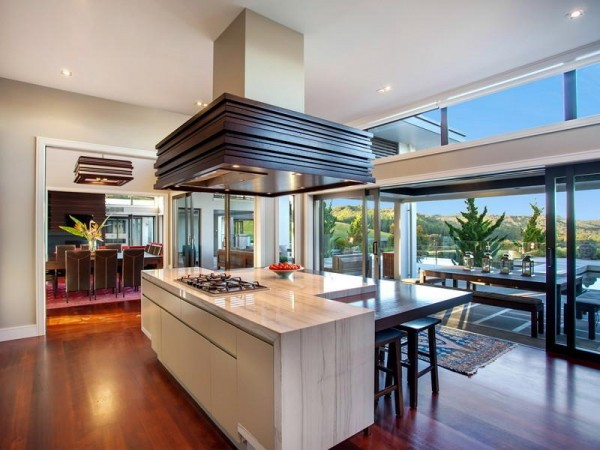 In the kitchen, a central island offers up yet another pretty place to perch for a snack, and a sliding door conceals a chef's kitchen complete with walk-in cool store.
