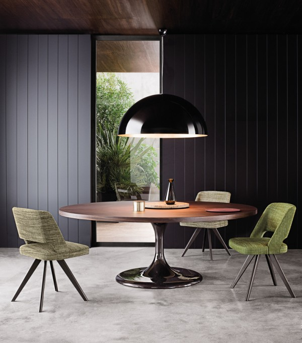A huge glossy pendant shade hangs in circular harmony with the round dining table beneath it. Subtle green dining chairs bring in a little of the natural shades from beyond the window pane.