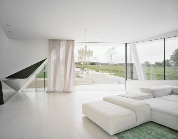 The interior of the home is light and bright, decorated in pure white paint, sheer curtains and pale furnishings.