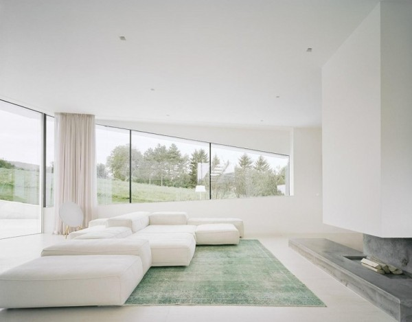 An area rug in the living room echoes the hues of the blanket of green grass beyond, and a slate gray fireplace continues the natural scheme.