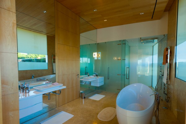 A large bathroom holds twin basins and a modern freestanding bath tub.
