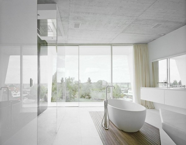 Up in the bathroom, a modern freestanding bath tub takes center stage in the large space, upon an attractive wooden floor treatment. The panorama stretching over the hillside beyond makes for peaceful bath time viewing.
