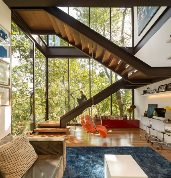 This open-sided staircase appears to climb the trees, and the suspended acrylic bubble chair beneath the treads looks at home amongst the branches too.