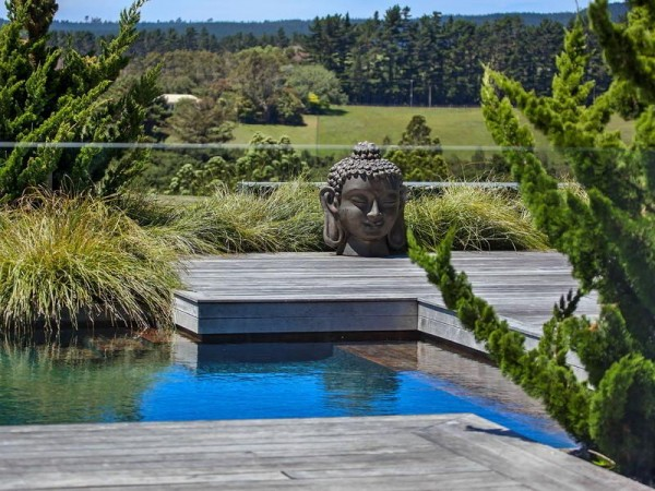 A wooden deck runs across the water to a zen platform, offering a serene spot for meditation in front of a giant statue of a Buddha head, and the stunning scenery beyond.