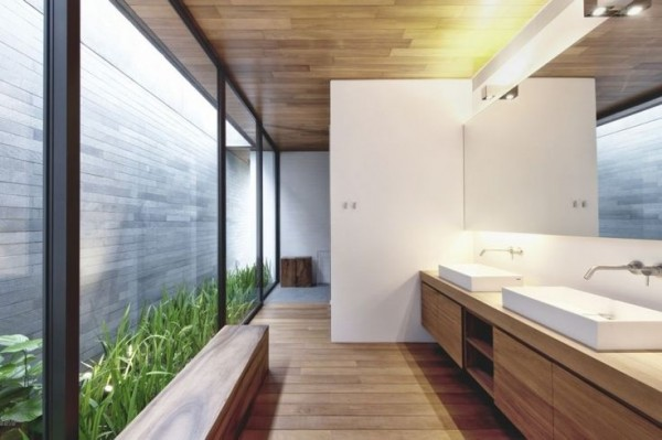 Nestled in a light well, a grassy border decorates this long bathroom space. The lush green strip brings a sense of health and well being–a perfect pick me up for the early morning routine.