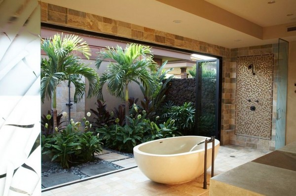 This bathroom enjoys a fuller garden complete with palm trees for a tropical bathing experience; you can even take a shower beneath the fronds.