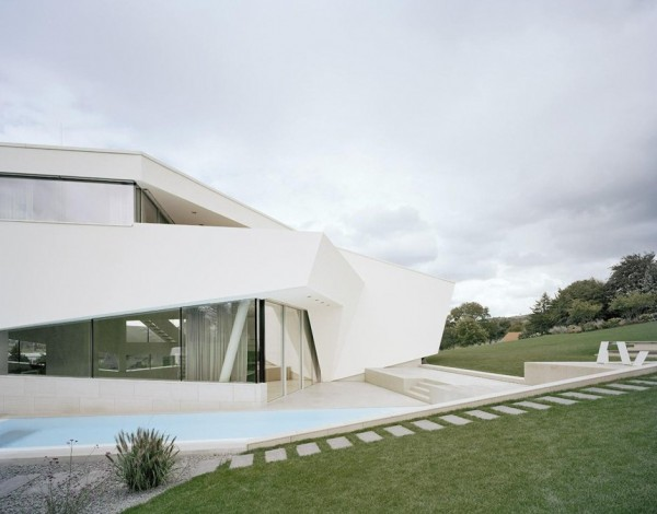 The homes private swimming pool nestles against the side of the dwelling, in the open air.