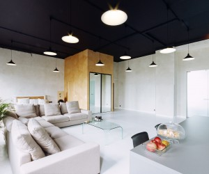 The overhaul covers a total area of 216 square meters, and embraces a very industrial style décor with black painted electrical ducts and simplistic lighting. Light gray is the color of choice throughout this apartment, but unusually the pale coarse-grained plaster walls have been teamed with black ceilings for a striking effect, which also prevents the overall look from becoming a plain box. The monochromatic scheme was chosen carefully to create a calm backdrop for the introduction of large colorful works of abstract art at a later date, as the investors envisaged this as a living space where exhibitions could be held, as well as meetings and various events.