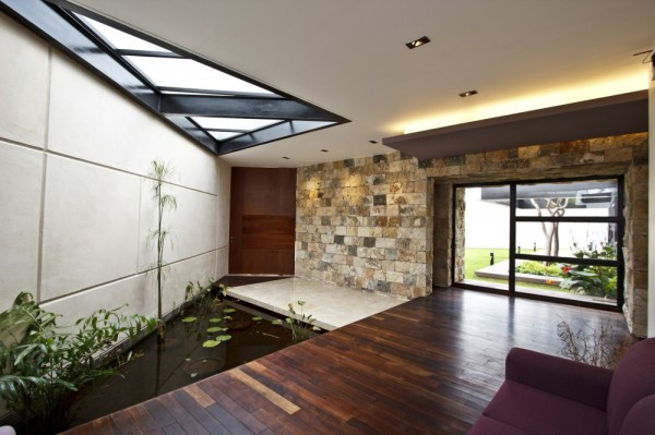 Once inside, nature continues its lively presence, and is nurtured by the sunlight that flows through large cutaway skylights. The decking area too seems to run on into the interior quarters, as wood planking has been selected in the entryway, complimented by stone tiling around the body of water.