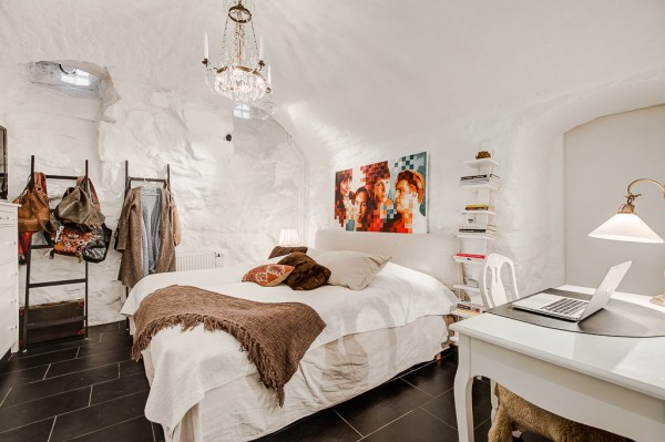 The colors from the living area are taken through into the bedroom, where coarse stoney walls give the slumber space a quaint cave-like atmosphere.